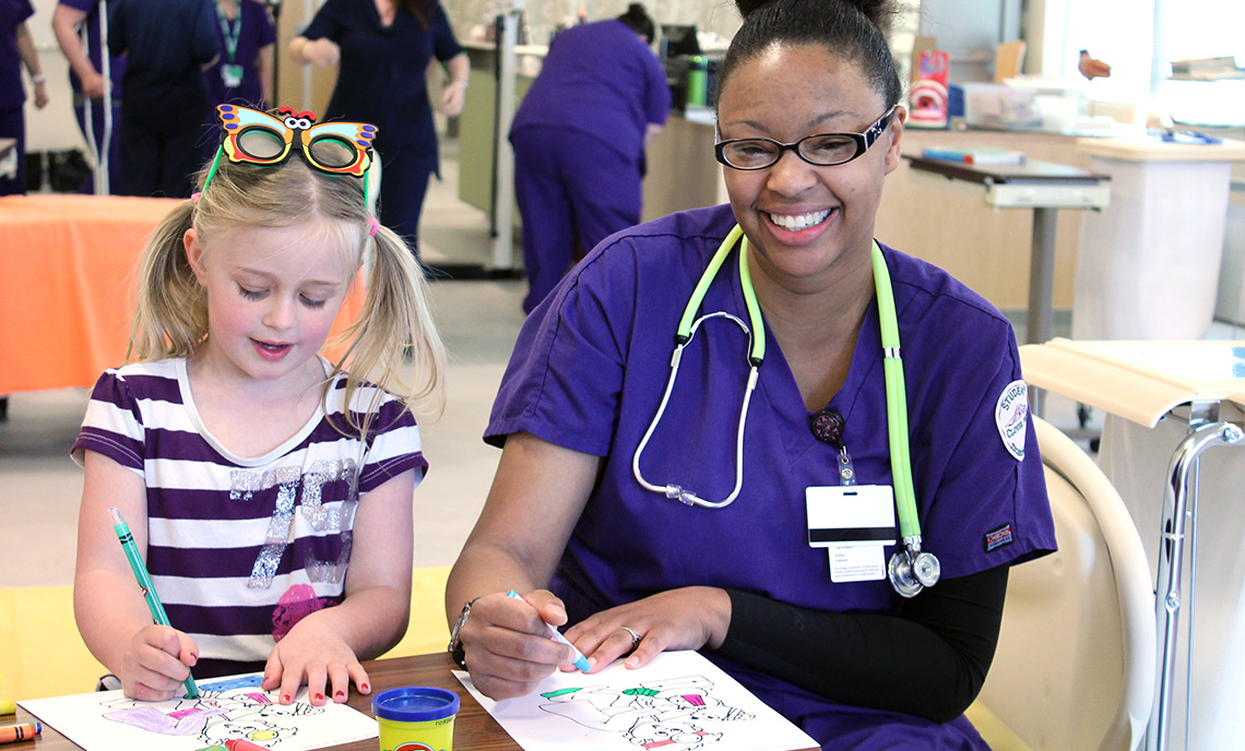 Nursing student Kristine Calloway colors with a child from Hayes Child Development Center.