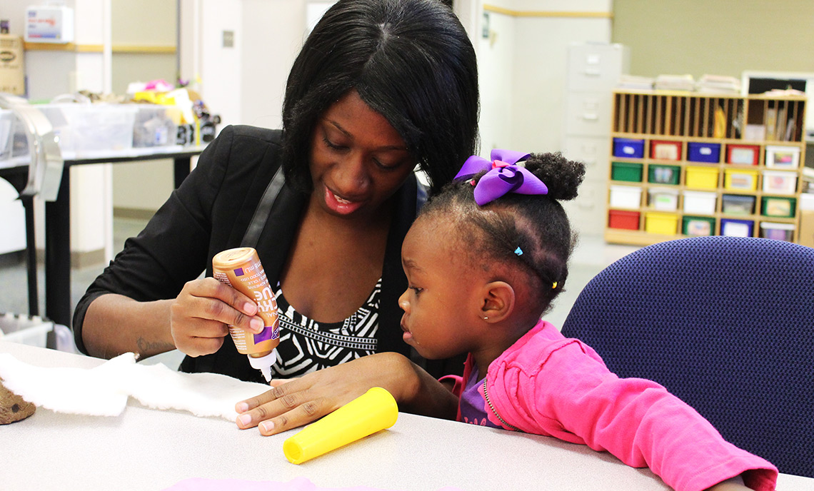 Lyric Anderson watches as her mother, Don-Necia, glues the fabric of her craft project.