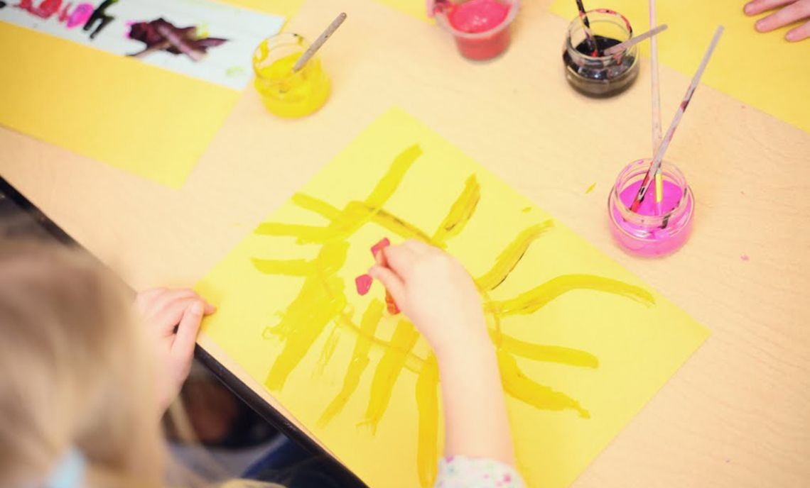 Child paints at a table in Hayse Childcare center