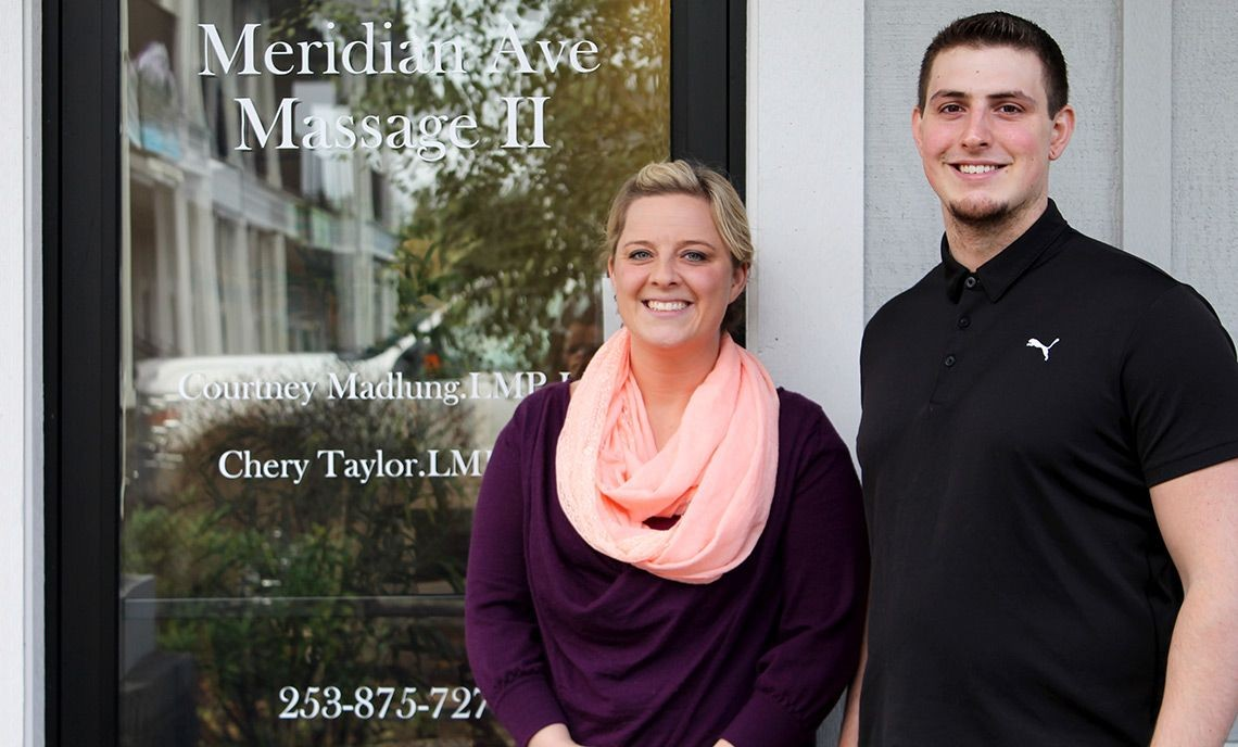 Massage Studies Program graduates Courtney Madlung and Scott Tupper stand in front of Meridian Ave. Massage in Graham.