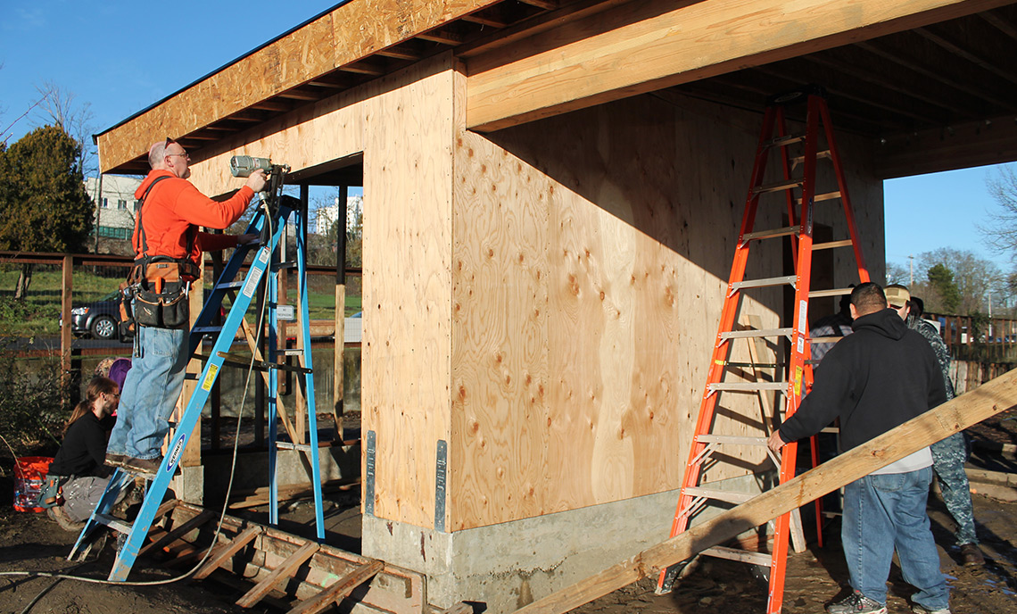 Dan Smith, left, and a group of his Residential Construction and Sustainable Building Science students work on the SHED in Tacoma during a recent lab day.