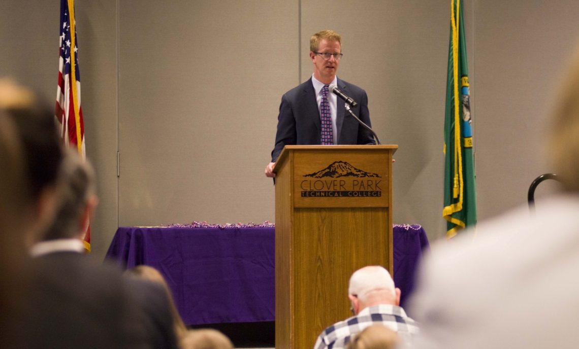 Congressman Derek Kilmer speaks at podium.