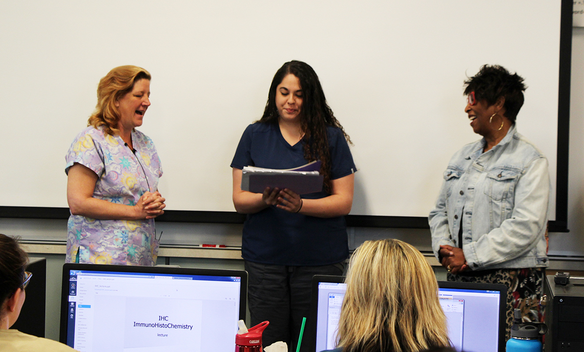 CPTC Medical Histology student Allison Hughes (center) opens the envelope containing her American Society of Clinical Pathologists National Honor Student Award during her morning class on May 17.
