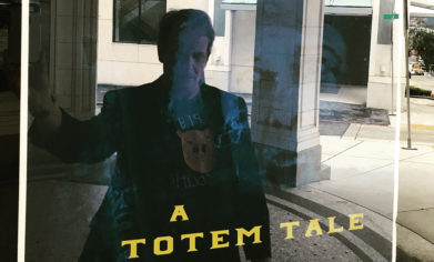 """CPTC alum Mick Flaaen can be seen in the reflection of the glass covering a poster promoting the premiere of his documentary """"A Totem Tale"""" at Tacoma's historic Rialto Theater."""