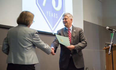 Lakewood Mayor Don Anderson shakes hands with Clover Park Technical College President Dr. Joyce Loveday and hands over a copy of the city's proclamation honoring the college.