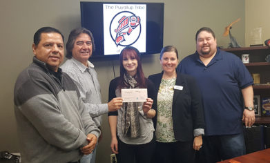 Puyallup Tribe chairman Don Coats, commissioner Brandon Reynon and vice-chair James Miles present the grant check to Heather Morgan and Rae Baghirov from the CPTC Foundation on Friday, Feb. 2.