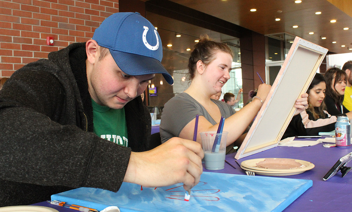 CPTC Dental Assistant student Jessica McElroy and her husband Robbie work on their sunflower paintings at ASG's Paint and Sip event on April 30.