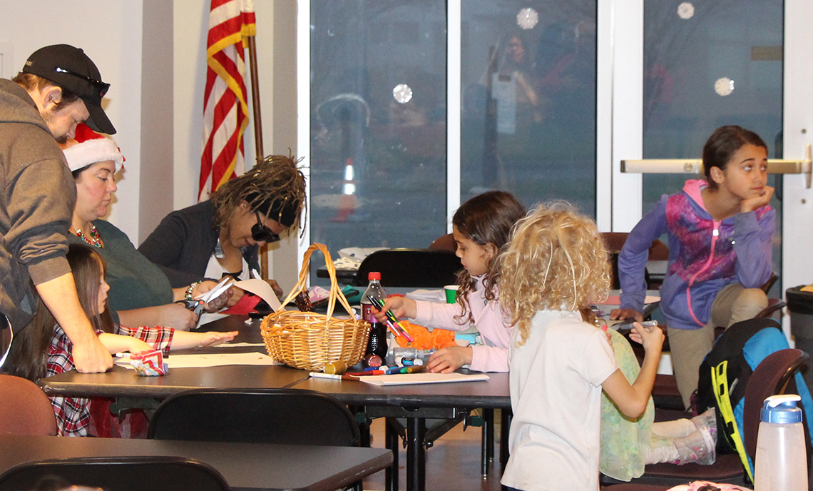 Erika Boquet and her children participate in a craft activity with Sheli Sledge at CPTC's Holiday House event in December 2017.