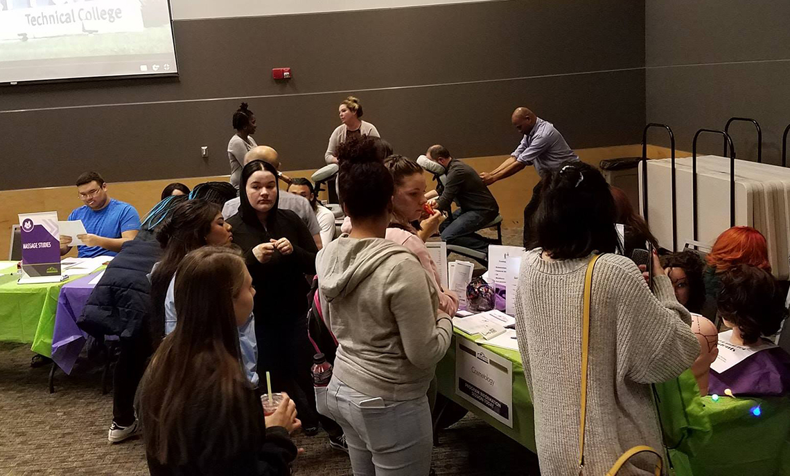 Visitors to CPTC's Fall Program Expo check out the Cosmetology and Massage Studies tables.
