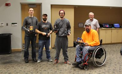 CPTC computer programming students (from left to right) Chad Drennan, Anthony McCann, Dakota Tominus, and Robert Wood join instructor Ken Meerdink to experiment with training their Donkey Cars.