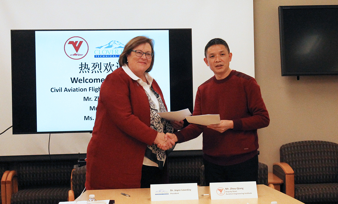 CPTC President Dr. Joyce Loveday and CAFUC Aviation Engineering Institute Deputy Dean Mr. Zou Qiang shake hands after signing a memorandum of understanding.