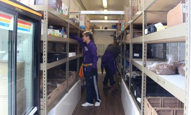 Mobile food bank visitors browse the food selection.