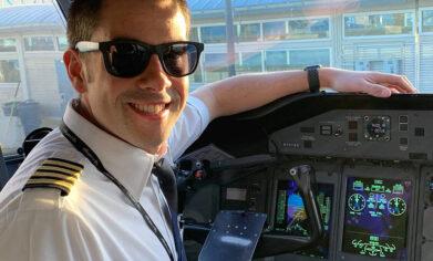 Man in pilot uniform sits in airplane cockpit