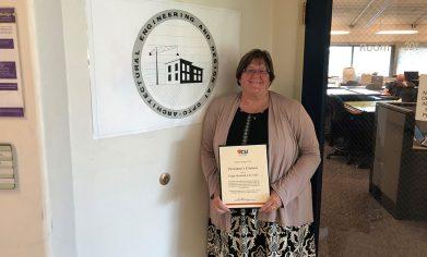 Women holds award in front of program sign