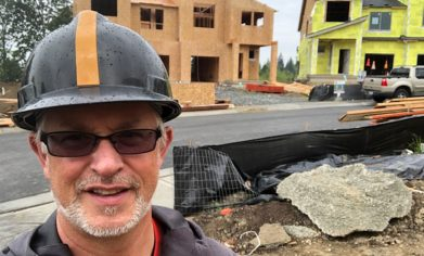 Man in a hard hat and sunglasses in the foreground with an active residential construction site behind.