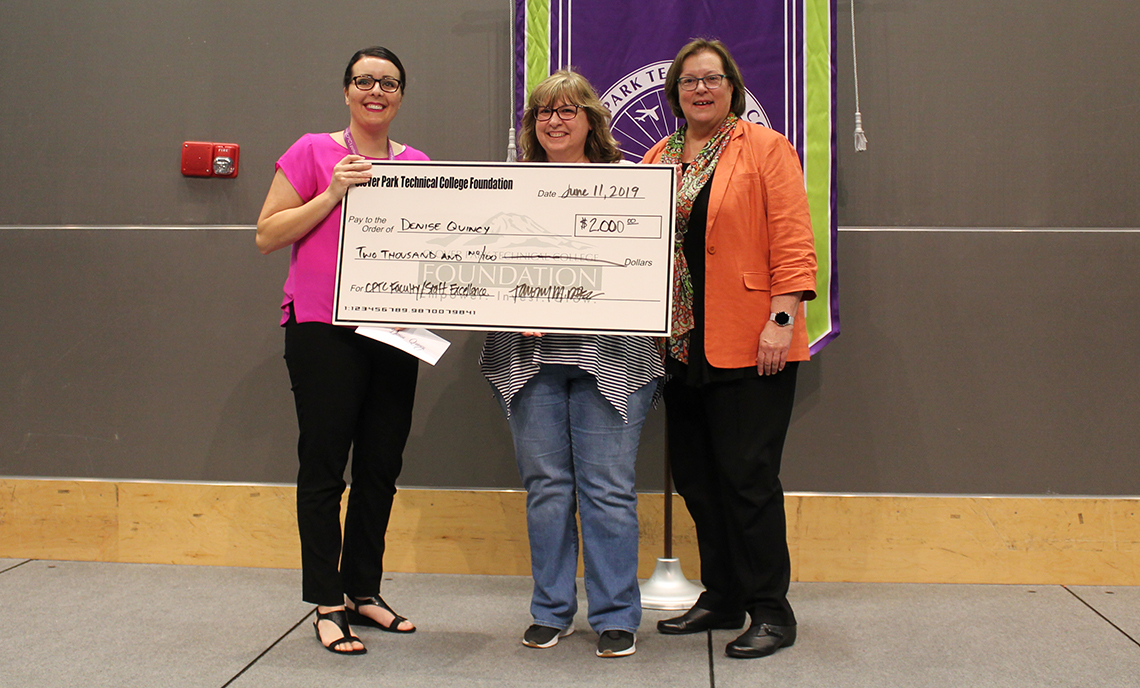 Three women holding a giant check