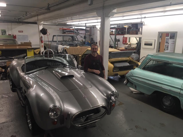 Andy Osborne standing next toa silver restored car in a garage.