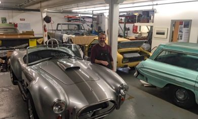 Any Osborn standing with classic cars in the garage of his business.