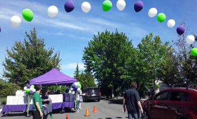 Arch of purple white and green ballons marking the starting line