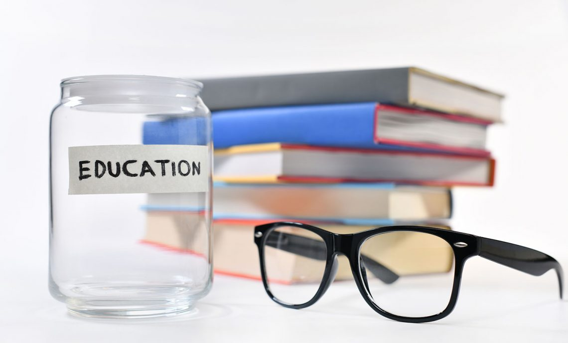 stack of books, glasses, empty jar with label says education
