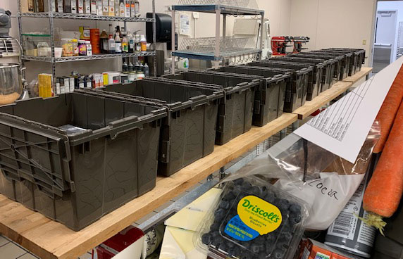 Black plastic containers in a row with assorted food in the bottom right corner