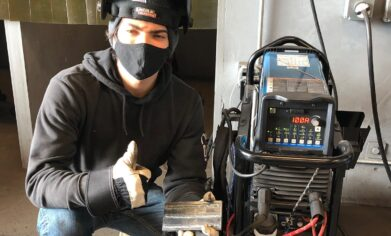 Smiling young man wearing a mask with welding equipment