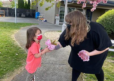 Rachael Butler handing a little girl flowers