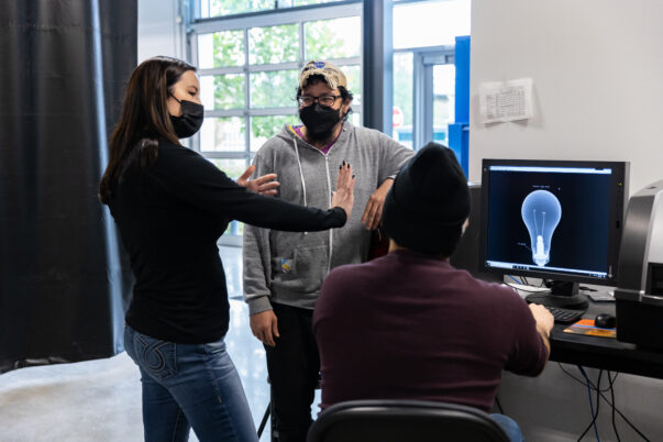 Megan Davey talking with two male students in from of a computer with a lightbulb on the screen
