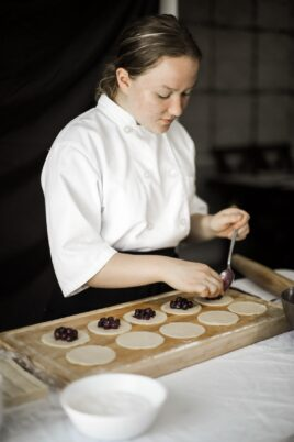Inessa Suparscaia scooping berries onto a tray of tarts