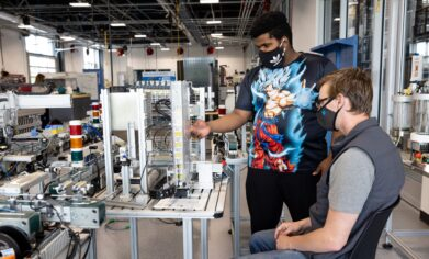 two students at mechatronics device